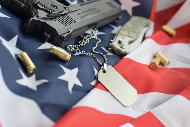 9mmの弾丸とピストルが入ったアーミードッグタグトークンは、折り畳まれた米国旗の上にあります Premium写真