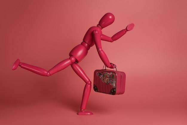 ピンクの背景に対してスーツケースとピンクの木製男を実行します Premium写真