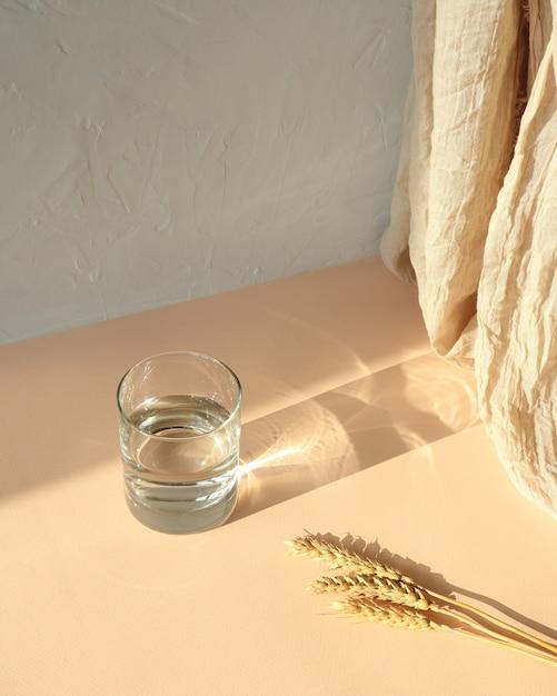 小麦、影とベージュのテーブルの上の水のガラス Premium写真