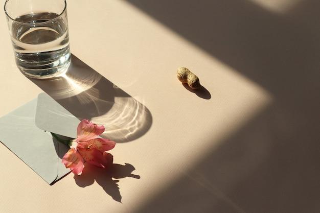 花、封筒、水、シャドウとテーブルの上のピーナッツ Premium写真