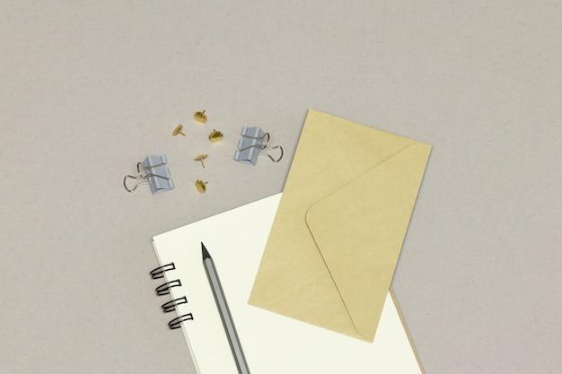 ノートブック、封筒、銀色の鉛筆&灰色の背景上のペーパークリップ Premium写真