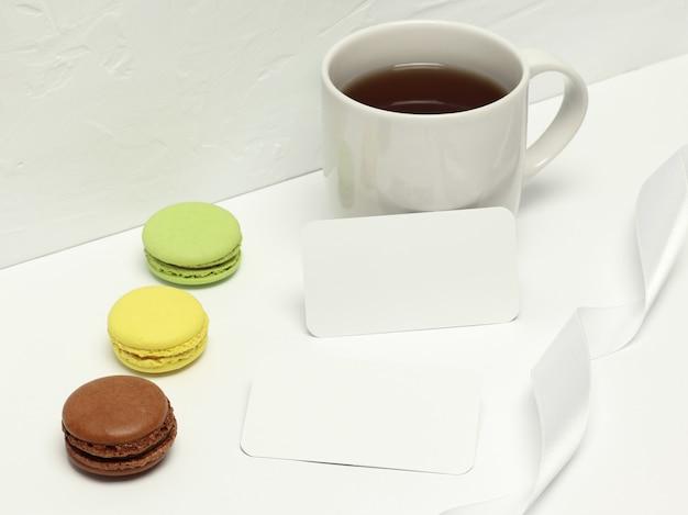 マカロン、リボン、一杯のコーヒーと白い背景の上の紙カード Premium写真