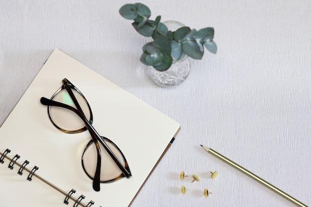 暗い眼鏡、金色のペン、ピンと緑の植物でメモ帳を開く Premium写真