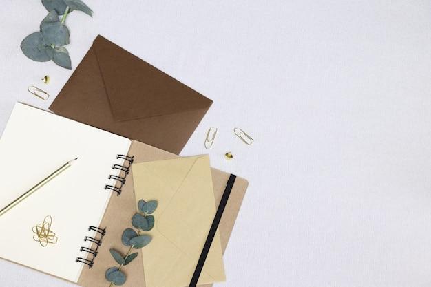 手紙を書く。開いたノート、封筒、金色の鉛筆、ペーパークリップ、ピン、ユーカリの枝 Premium写真