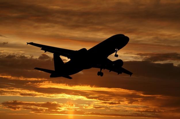 Самолет, летящий на закате Premium Фотографии