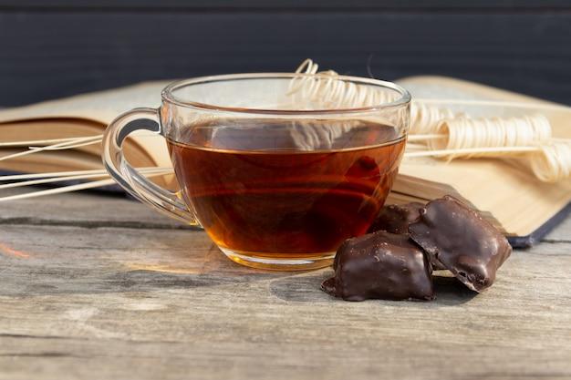 Чашка чая с открытой книгой и шоколадные конфеты на деревянный стол. Premium Фотографии