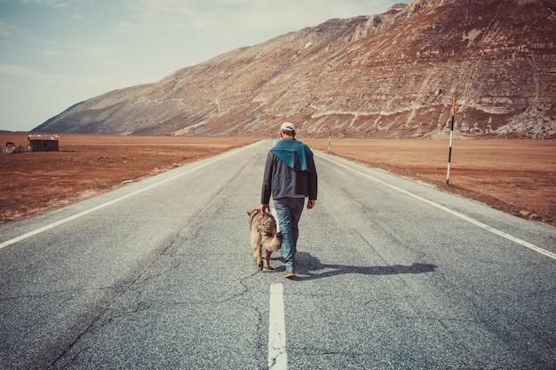 山の中の彼の犬と一緒に道を歩いて男 Premium写真