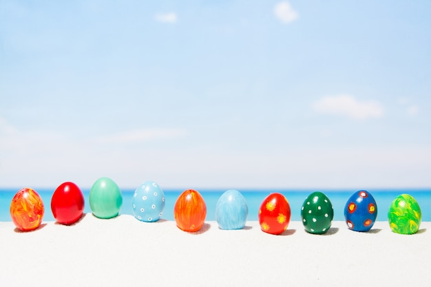 Пасха на фоне тропического пляжа. яйца на белом песке. концепция отдыха и путешествий весной Premium Фотографии