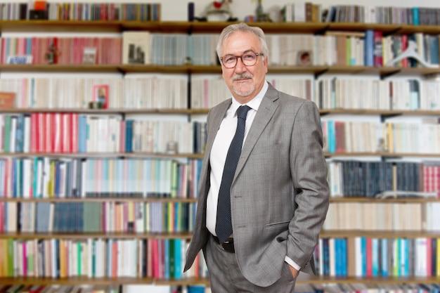 Старший учитель стоял с книгой перед книжным шкафом Premium Фотографии
