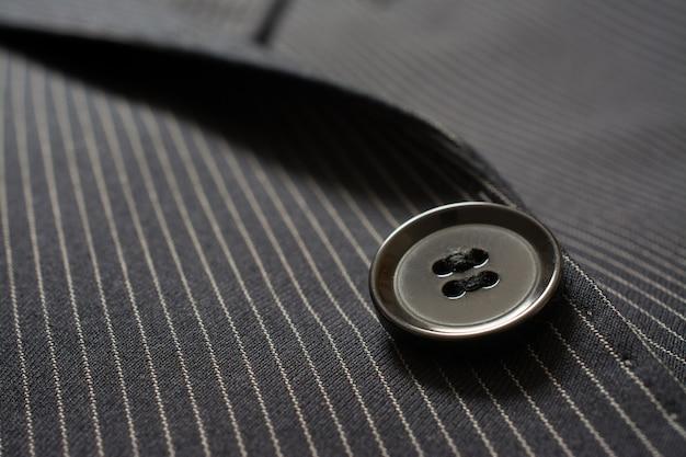 ピンストリップ布のスーツボタンのクローズアップの詳細 Premium写真
