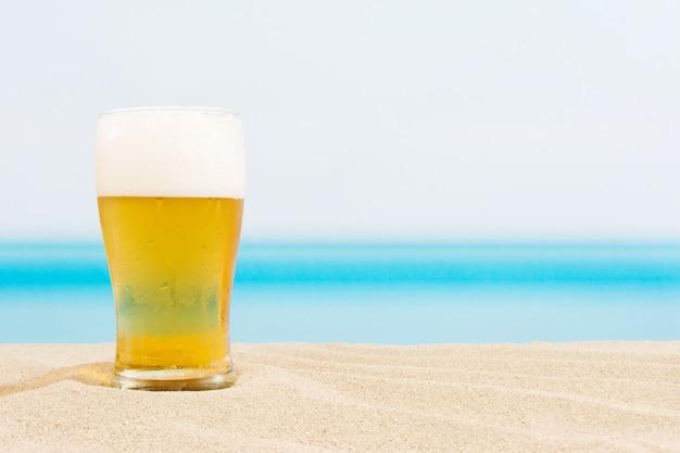 ビーチの背景にビール Premium写真