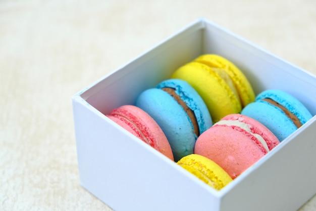 白いギフトボックスにカラフルなフランスの甘いケーキマカロン。カフェやベーカリーの広告用。 Premium写真