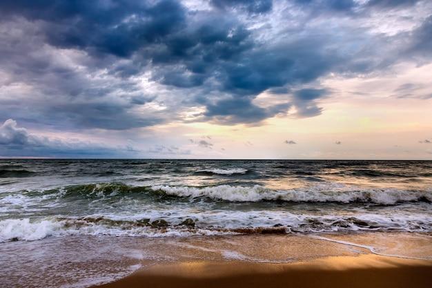 朝の海景に劇的な空。砂浜のビーチで嵐。 Premium写真