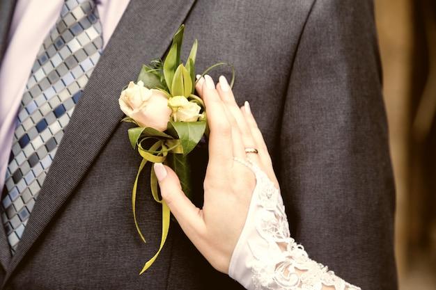 新郎のジャケットにブートニアを調整する花嫁のハング Premium写真