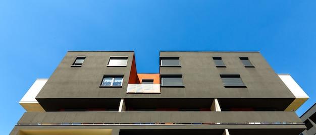 青い空にモダンな黒いアパートの建物の外観 Premium写真