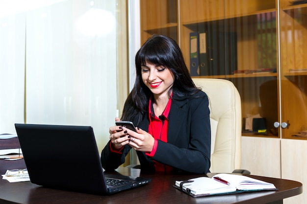 オフィスの机に座って携帯電話を持つ若い女 Premium写真