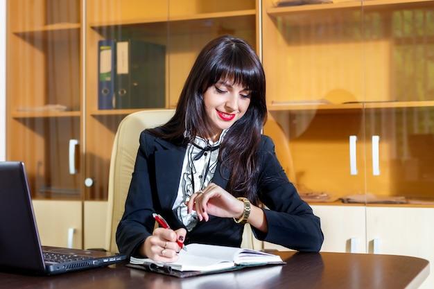 オフィスで働く女性と彼の時計を見て笑顔の女性 Premium写真
