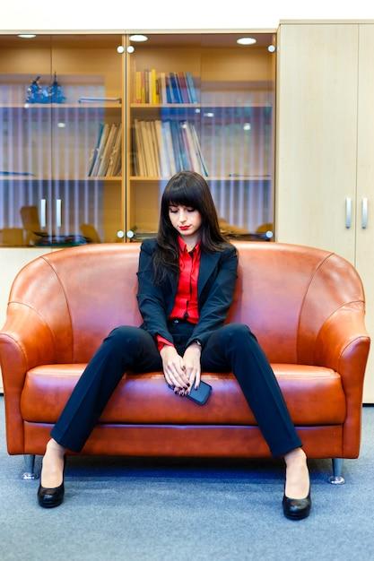 ソファの上のオフィスに座っているスーツで素敵な思いやりのある実業家 Premium写真