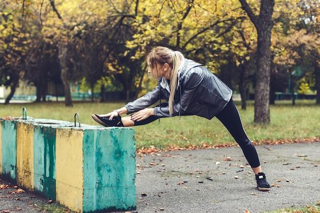 雨の日に都市公園でストレッチ体操を行う美しい若い女性。 Premium写真