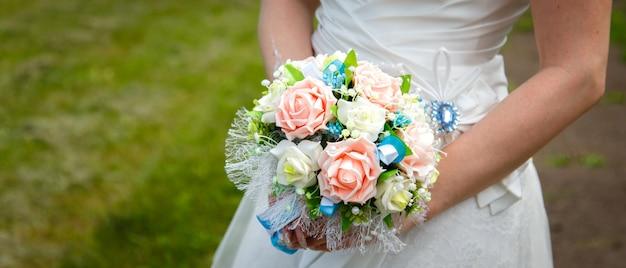 緑の芝生の背景に花嫁の手の中のウェディングブーケ Premium写真