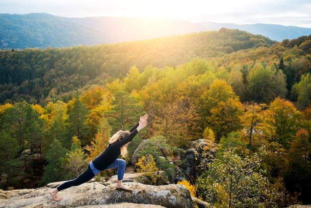 スポーティなフィット女性は山の上にヨガを練習します。 Premium写真
