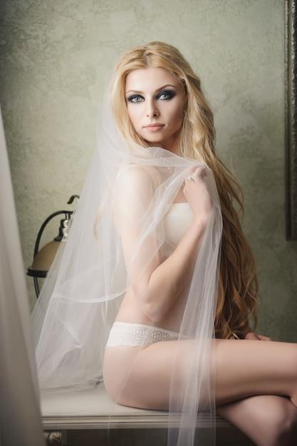 Красивая невеста в нижнем белье и фате в день свадьбы Premium Фотографии