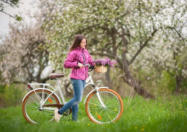 春の庭でビンテージ白い自転車を持つ女性サイクリスト Premium写真