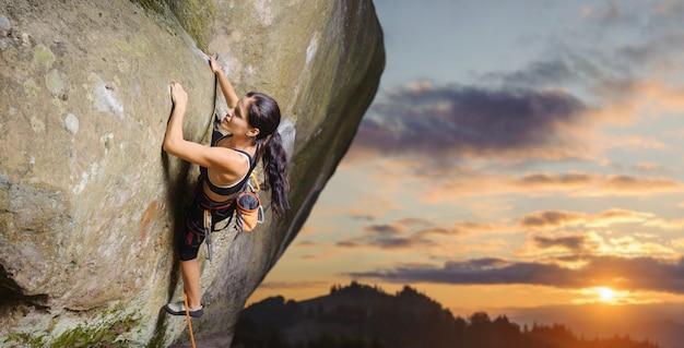 急な岩壁に挑戦的なルートを登る若い魅力的な女性ロック・クライマー Premium写真