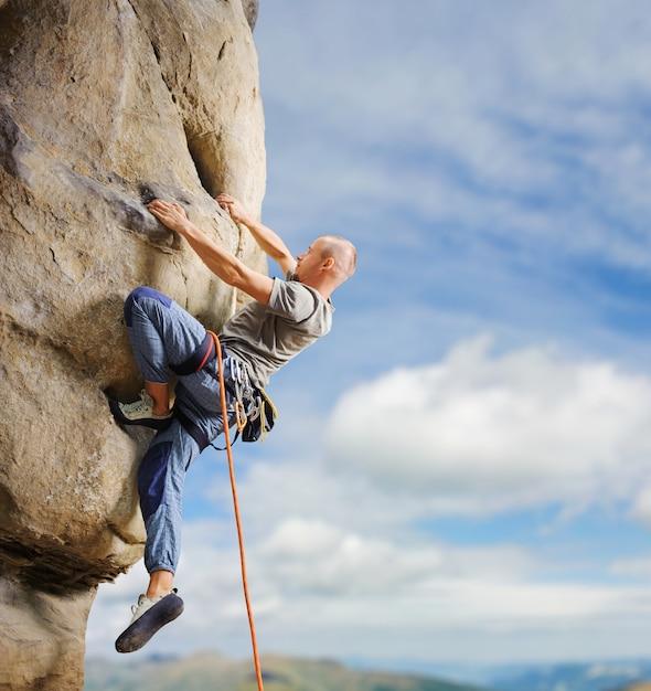 ロープで自然の中で大きな岩を登る男性クライマー Premium写真
