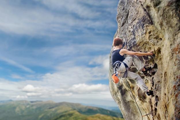 急な張り出して岩崖の上の女性ロック・クライマー Premium写真