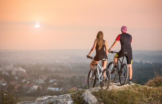 丘の上に立っているマウンテンバイクと背面の男性と女性のバイカー Premium写真