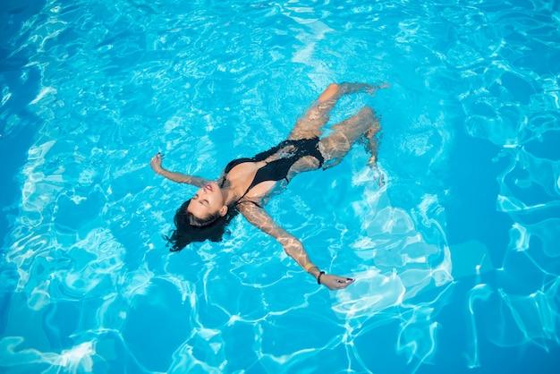 スイミングプールで彼女の背中に浮かぶとリラックスした黒の水着の魅力的な女性 Premium写真