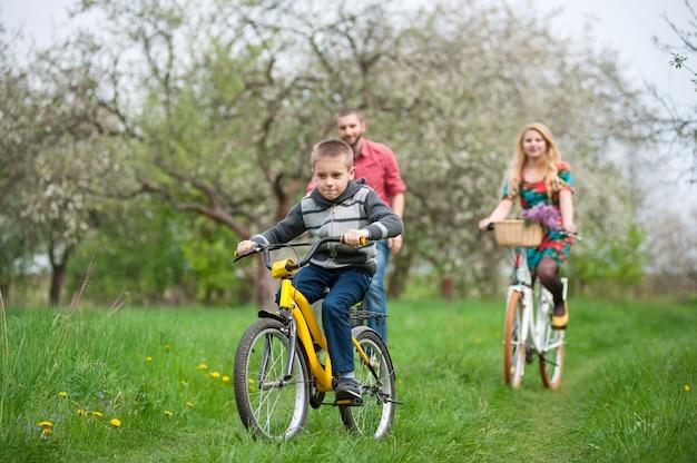 春の庭で自転車に幸せな家族 Premium写真