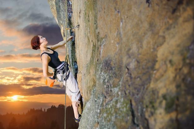 岩が多い壁にロープで登山の女性クライマー Premium写真