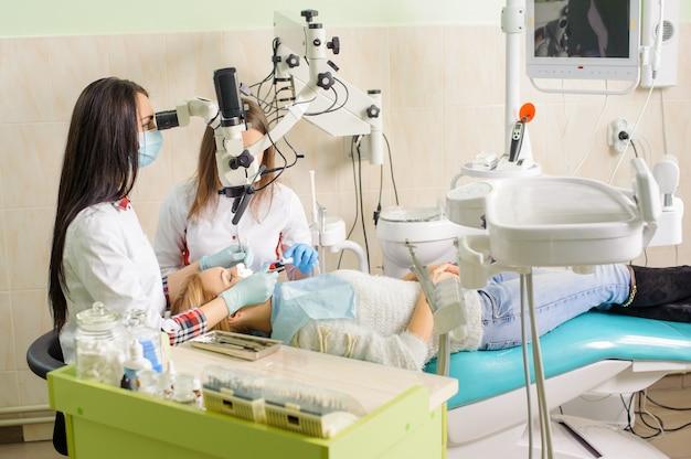 歯科医のオフィスで顕微鏡を使用して齲蝕を治療する女性歯科医 Premium写真