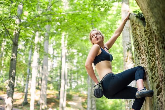屋外の大きな岩に登る若い女性 Premium写真