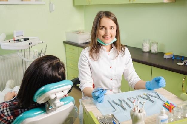 歯を固定するための歯科用デバイスを保持している女性歯科矯正医 Premium写真