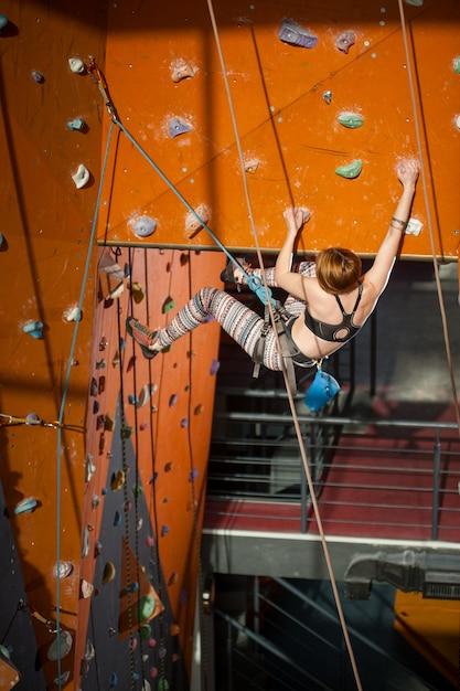 特別な装備を備えた女性登山家が屋内のロッククライミングウォールに登る Premium写真
