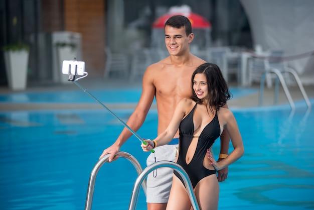 スイミングプールに対してポーズ完璧なプロポーションと若いカップルのクローズアップの肖像画 Premium写真