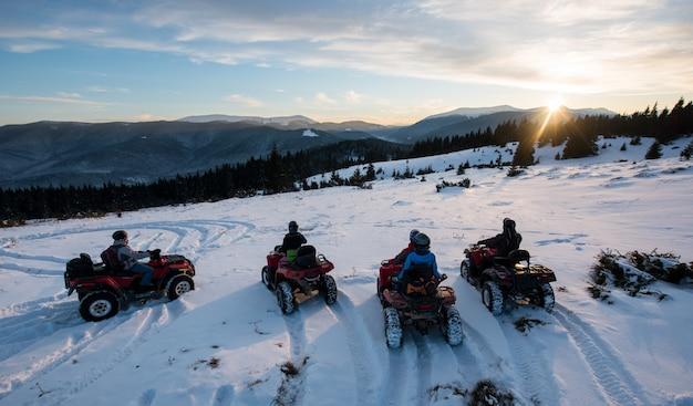 オフロードクワッドバイクに座って、冬の山の美しい夕日を楽しむ人々のグループ Premium写真