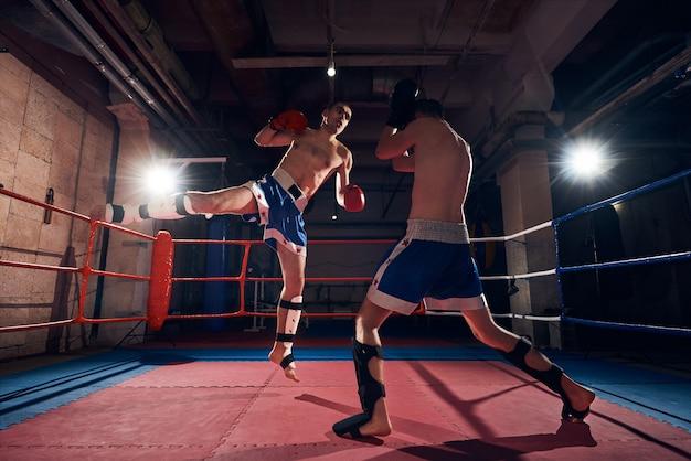 ヘルスクラブのリングでキックボクシングをトレーニングするボクサー Premium写真