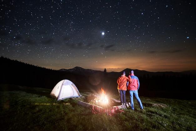 夜の星空の下でキャンプファイヤーとテントの近くの観光客 Premium写真