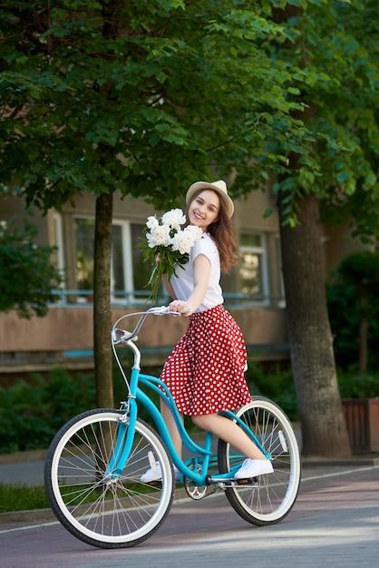牡丹とレトロな自転車で素敵な女性が一緒に乗っています。 Premium写真