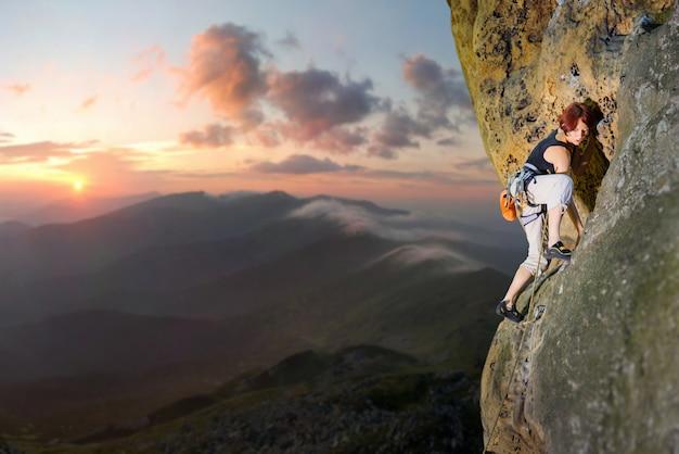 岩の壁に挑戦的なルートを登る女性ロック・クライマー Premium写真