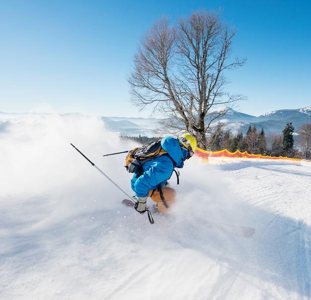 Снимок заднего вида лыжника, едущего вниз по склону на горнолыжном курорте в карпатах сезонная деятельность спорт спортсмен хобби отдых концепция путешествия Premium Фотографии
