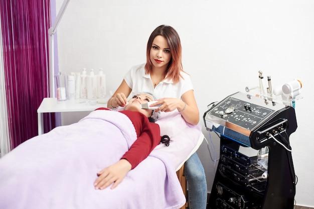 Врач с ультразвуковым скрабером проводит ультразвуковой кавитационный пилинг лица для женщины. процедура ультразвуковой чистки лица. косметологическая клиника. Premium Фотографии