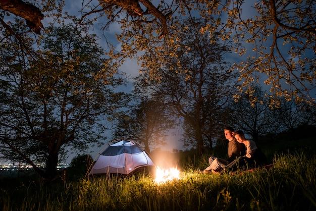 Романтическая пара туристов, сидящих у костра возле палатки, обнимали друг друга под деревьями и ночным небом. ночной кемпинг Premium Фотографии