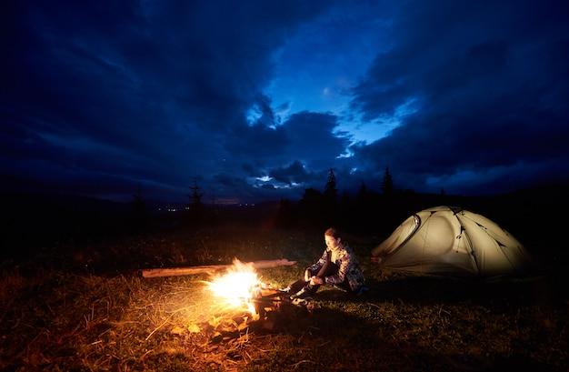 若い女性のバックパッカーは、山でのキャンプを楽しんで、燃えるキャンプファイヤーの近くに座って、美しい夜の曇り空の下で観光テントを照らしました。観光、野外活動のコンセプト Premium写真