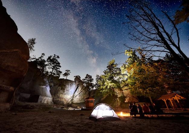 夜のキャンプ、キャンプファイヤー、テントの横で休んでいる友人ハイカー Premium写真
