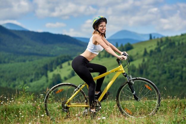 Взгляд со стороны женского всадника задействуя на желтом горном велосипеде на траве, наслаждаясь солнечным днем. горы, леса и голубое небо спорт на свежем воздухе Premium Фотографии